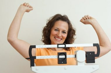 After losing weight with CircaSlim happy woman stands on scale in victory