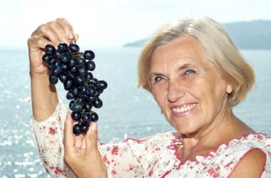 Senior woman holding a bunch of resveratrol rich grapes to fight cognitive decline