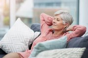 Emotionally stable senior woman relaxes on sofa