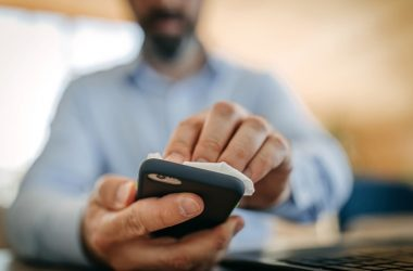 Man cleaning his dirty cellphone contaminated with viruses, bacteria, and maybe coronavirus