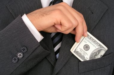 Close up of Big Pharma executive putting money into his suit pocket for coronavirus study