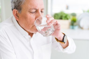 Senior man drinking a glass of water to combat dry mouth