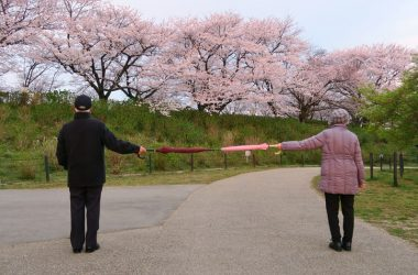 A man and woman socialize at a distance in a park to avoid loneliness