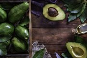 Sliced avocado with fruits in a crate and avocado oil on a wooden table