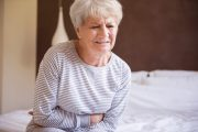 Woman with gut inflammation and pain holds belly