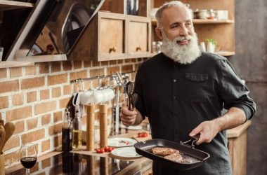 Senior man cooking steaks with saturated fat